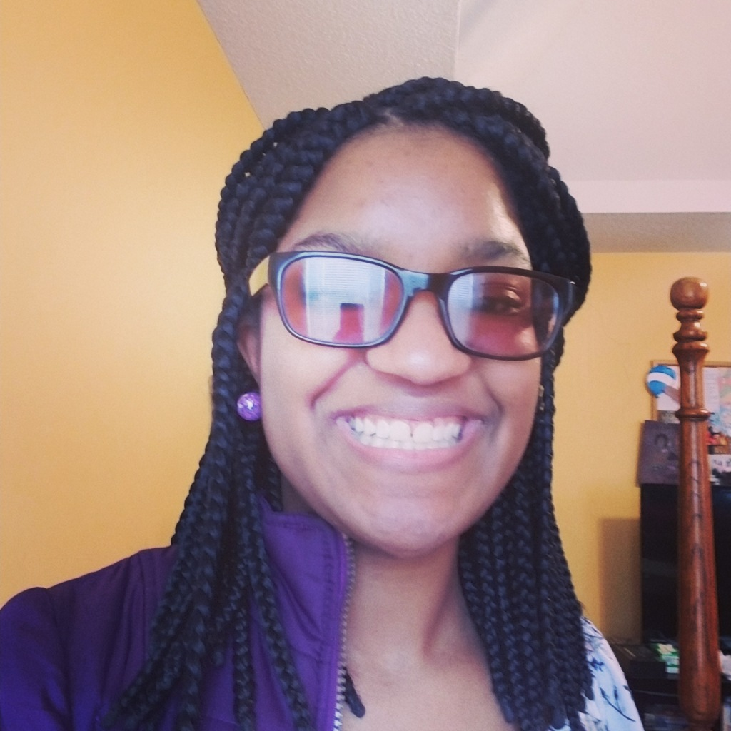 Girl in sunglasses and purple jacket smiles at camera in room